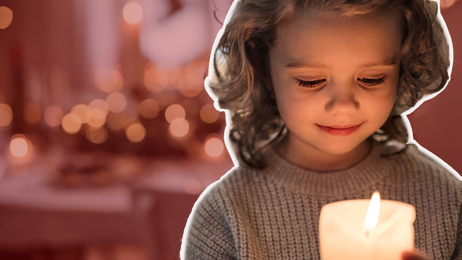 Young child holds a lit candle with christmas decorations in the background